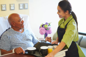 nurse serving food to an elderly man